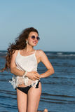 Woman kneeling in sea water wear bikini, sunglasses and white shirt Stock Photos