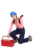 Woman kneeling by tool box Royalty Free Stock Photos