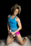 Woman kneeling in white powder in a blue tank top curl weight Royalty Free Stock Images