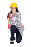 Woman kneeling with wrench Royalty Free Stock Photography