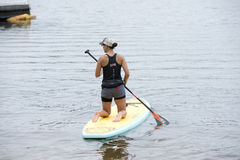 Woman kneels on a paddleboard in the bayou Stock Photos