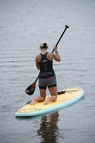 Woman kneels on a paddleboard in the bayou. Woman is kneeling on a paddleboarding in Bayou Texar in Pensacola, Florida Royalty Free Stock Image
