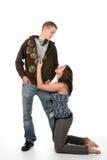 Woman on knees next to grunge boyfriend. Woman on her knees looking up at her grunge boyfriend royalty free stock image