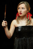 Woman with knife. Beautiful woman with knife. She is terrified.  Black background Royalty Free Stock Photography