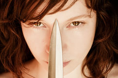 Woman and knife. Young woman portrait staring at camera with a knife Stock Photography