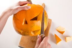 Woman with knife cuts pumpkin for Halloween holiday stock photos