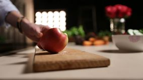 Woman with knife cutting apple on chopping board stock video footage