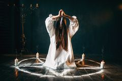 Woman with knife sitting in pentagram circle. Woman with knife in hands sitting in pentagram circle with candles. Dark magic ritual, occultism and exorcism royalty free stock photography