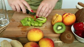 Woman with a knife regimen of a peach for fruit salad. Hd shot with dolly from left to right stock video footage