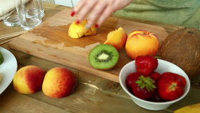 Woman with a knife regimen peach for fruit salad. Woman with a knife regimen of a peach for fruit salad. Hd shot with dolly from left to right stock footage