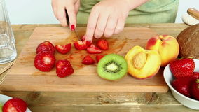 Woman knife regimen of strawberries for fruit salad. Hd shot with dolly from left to right stock footage