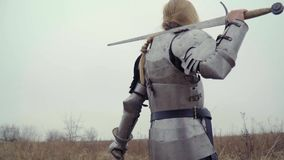 Jeanne d`Arc in armor with a sword on his shoulder stands in the field and looks out for enemies. Woman knight in armor with a sword in the field stock footage