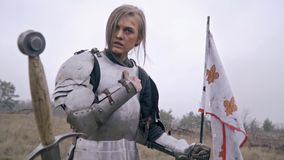Wounded Jeanne D`ark kneels leaning on the flag and sad about the fallen comrades, slow motion. Woman knight clasps his hand to her chest and sad stock video