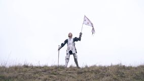 Masculine Jeanne d`Arc in armor stands on a hill and waving a flag, slow motion. Woman knight leans on sword and waving flag stock video