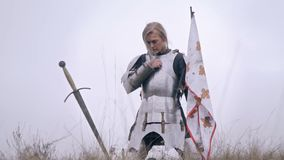Grieving Jeanne D`ark kneels holding the flag and pressing his hand to her chest, slow motion. A woman knight is sad about fallen soldiers stock video