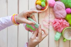 A woman knits a bright colored canvas with spokes. Hands close-u Royalty Free Stock Images