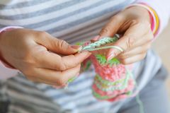 A woman knits a bright colored canvas with spokes. Hands close-u Royalty Free Stock Image