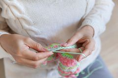 A woman knits a bright colored canvas with spokes. Hands close-u Royalty Free Stock Photography