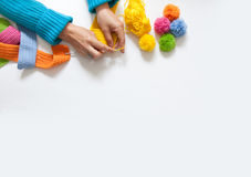 The woman knits a hook colored fabric. View from above. Colored threads and pompoms Stock Images