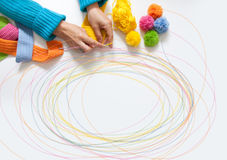 The woman knits a hook colored fabric. View from above. Colored threads and pompoms Royalty Free Stock Photos