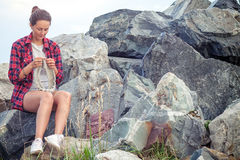 Woman knits with knitting needles a gray sweater. A beautiful dark-haired woman in a plaid shirt, denim shorts, white sneakers knits with knitting needles a gray Stock Images