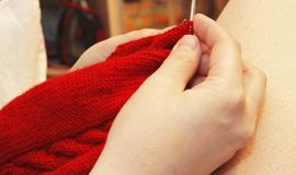 Woman knits with knitting needles red sweater from natural woole. A Woman knits with knitting needles red sweater from natural woolen threads closeup Stock Photos