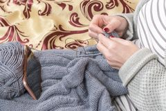 Woman knits while looking at the phone royalty free stock photo