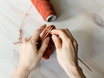 Woman knits a pattern on table. Crafting scene: woman knits a pattern on table, surrounded by threads Stock Images