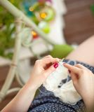 A woman knits a white canvas with spokes. Hands close-up. Royalty Free Stock Images