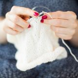 A woman knits a white canvas with spokes. Hands close-up. Stock Image