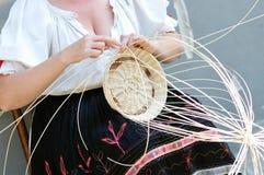 Woman knits wicker basket Royalty Free Stock Photo