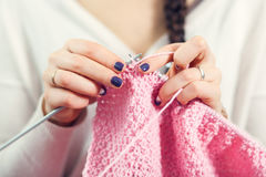 Woman knits woolen clothes. The woman knits woolen clothes. Knitting needles. Close-up. natural wool Royalty Free Stock Images