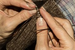 A woman knits woolen socks with knitting needles. Women`s hobby Royalty Free Stock Image