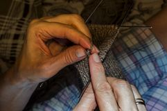A woman knits woolen socks with knitting needles. Women`s hobby Royalty Free Stock Photos