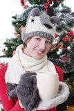 Woman in knitted hat and mitten under Christmas tree with cup. Smiling woman in knitted hat and mitten under Christmas tree with cup, focus on woman Royalty Free Stock Photos