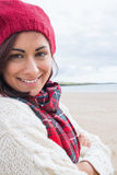 Woman in knitted hat and pullover smiling at beach Stock Photography
