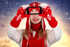 Woman in a knitted hat scarf and mittens takes pictures of herself on the phone Stock Image