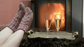 Woman in knitted socks feet warm by the fireplace. On the tray are two glasses of champagne stock video footage