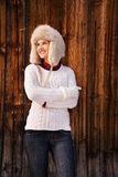 Woman in knitted sweater and furry hat standing near wood wall Royalty Free Stock Photo
