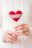 Woman in knitted sweater holding a felt red heart Stock Photos