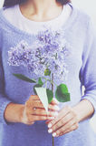 Woman in knitted sweater holding lilac flower in her hands Stock Photo