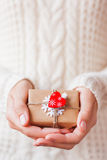 Woman in knitted sweater holding a present with red heart. Stock Image