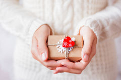 Woman in knitted sweater holding a present with red heart. Royalty Free Stock Photography