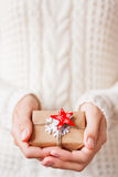 Woman in knitted sweater holding a present with red star. Royalty Free Stock Photo