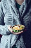 Woman in knitted sweater holding raw pie. Woman in knitted sweater holding raw persimmom squash pie Royalty Free Stock Images