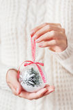 Woman in knitted sweater holds a christmas decoration. Stock Images