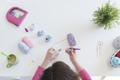 Woman knitting bootees for a baby boy at her studio Stock Photo