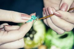 Woman knitting a crocheted flower from blue threads against a ba Royalty Free Stock Photography