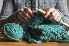 Woman knitting green woolen scarf Royalty Free Stock Image