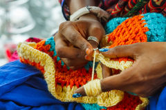 Woman knitting a mat. Hands of Indian woman knitting a mat royalty free stock image